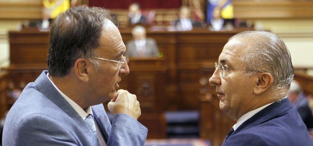 El portavoz del grupo Socialisata, Francisco Manuel Fajardo (i), conversa con el diputado del PP Emilio Moreno, durante la tercera jornada del pleno del Parlamento de Canarias.