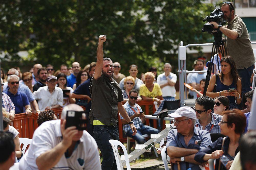 """Un joven gritando en catalán """"independencia, socialismo"""", con el puño en alto y tirando octavillas de la agrupación Arran de la CUP."""