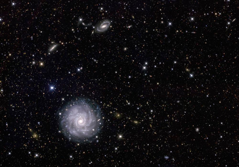 Fotografía del cielo profundo tomada por el equipo del Dark Energy Survey desde el Telescopio Blanco en Cerro Tololo, Chile. En primer plano aparece la galaxia NGC1703. A su alrededor podemos detectar muchas otras galaxias: la mayoría de ellas se encuentran a distancias mucho mayores que la principal y por eso las vemos más pequeñas. Estas galaxias lejanas son la imagen de cómo era el Universo en un pasado remoto, ya que la luz tarda millones de años en llegar hasta nosotros. DARK ENERGEY SURVEY.