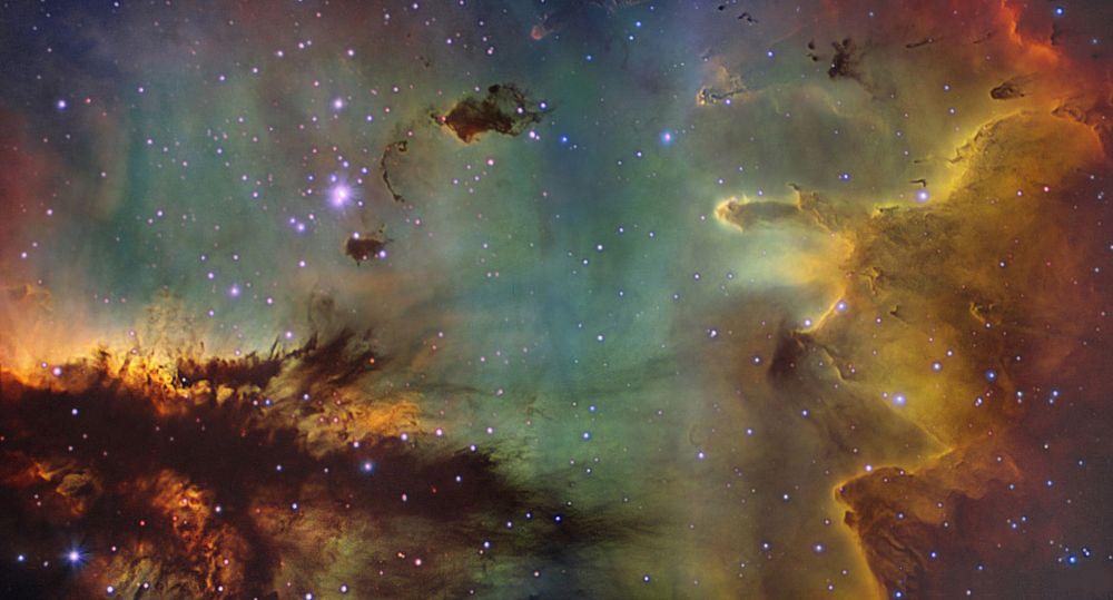 """Imagen de una región de la nebulosa NGC 281, una """"guardería estelar"""" de nuestra galaxia, a unos 9000 años luz de distancia. Podemos distinguir un pequeño cúmulo de estrellas jóvenes, la nebulosa de gas difuso iluminada por esas estrellas y largas estructuras oscuras de gas y polvo, algunas de ellas en forma de pilares en los que nuevas estrellas pueden estar formándose. La imagen es una combinación de tres filtros que muestran la emisión de tres líneas espectrales: H-alfa (hidrógeno, en color rojo), [N II] (nitrógeno, en verde) y [O III] (oxígeno, en azul), y ha sido obtenida con el telescopio IAC80, del Observatorio del Teide (Tenerife). Daniel López (www.elcielodecanarias.com) e IAC."""