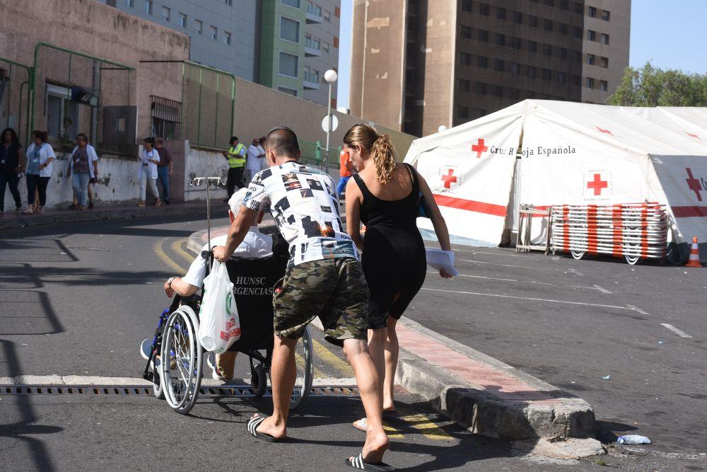 Dos personas llevan a un enfermo en silla de ruedas para ingresar por Urgencias ante el hospital de campaña instalado a la puerta del servicio.