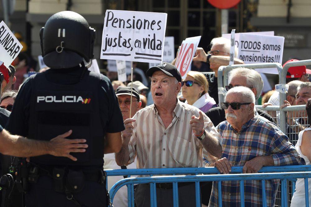 Grupos de pensionistas que se concentraron hoy en el Congreso de los Diputados pidiendo mejoras en sus prestaciones intentan romper el cordón policial.