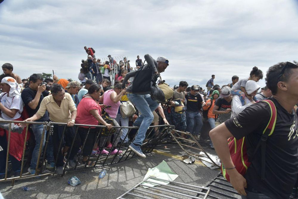 Miles de migrantes hondureños logran librar la valla que une la frontera con Guatemala para ingresar a México en el margen del Río Suchiate hoy, viernes.