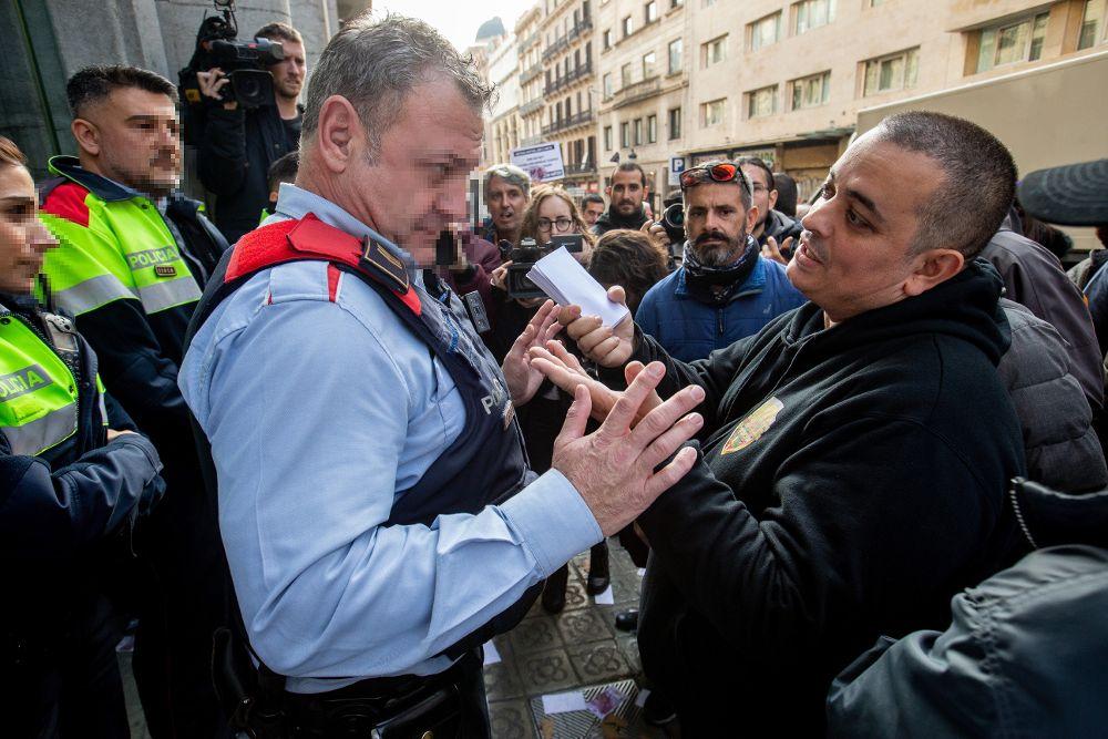 """El portavoz y cabeza visible de la asociación de taxistas Elite Taxi, Alberto """"Tito"""" Álvarez (d), conversa con varios mossos d'esquadra."""