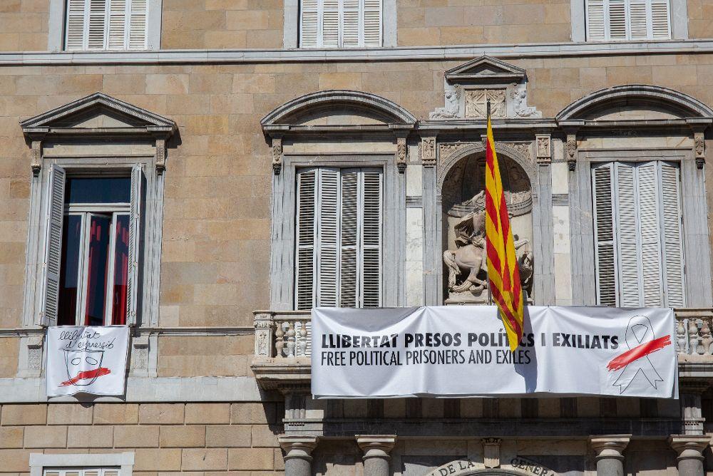 Balcón del edificio de la Generalitat con pancarta con lazo blanco y franja roja por presos políticos un día después de que el president, Quim Torra, acatara la orden de la Junta Electoral.